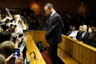 "Oscar Pistorius stands at the dock before the start of proceedings at a Pretoria magistrates court February 22, 2013. ""Blade Runner"" Pistorius, a double amputee who became one of the biggest names in world athletics, was applying for bail after being charged in court with shooting dead his girlfriend, 30-year-old model Reeva Steenkamp, in his Pretoria house.  REUTERS/Mike Hutchings (SOUTH AFRICA - Tags: CRIME LAW SPORT ATHLETICS TPX IMAGES OF THE DAY) - RTR3E3ZO"